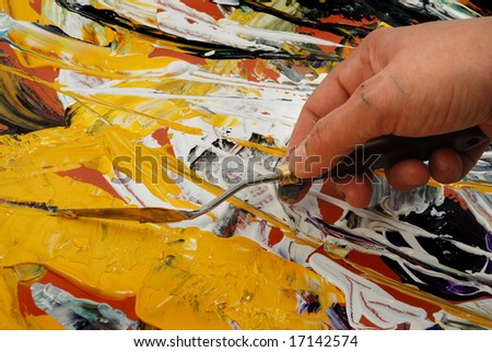 Woman hand painting in yellow  with spatula