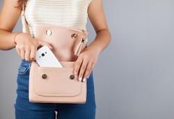 Woman hand phone on bag pocket.