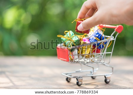 Woman hand picking mini gift box from the red shopping cart. Concept of online shopping, festive, unboxing, and Christmas eve and new year sale.