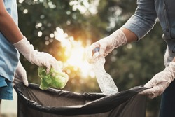 woman hand picking up garbage plastic for cleaning at park