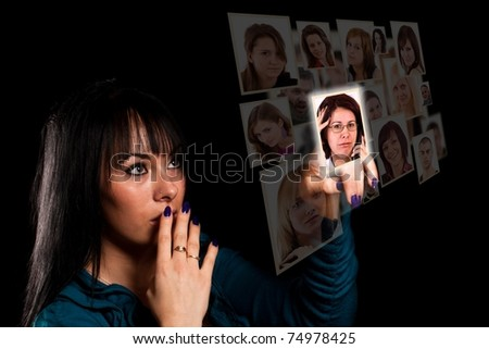 woman hand pressing digital display with faces in black backgound, focus on hand