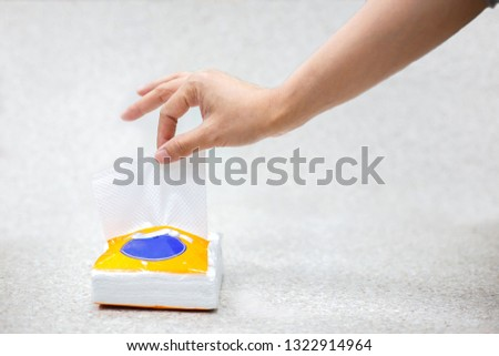 Woman hand pulling out white tissue paper from tissue box for cleaning something on gray background. #1322914964