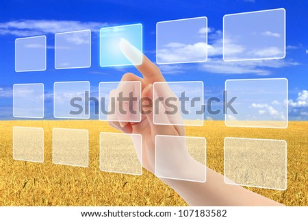 Woman hand pushing virtual icons on interface over wheat field and blue sky landscape