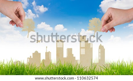 Woman hand put Paper cut of tree over  city and grass with blue sky