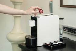Woman hand puts a capsule in coffee machine, capsule coffee maker.