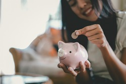 Woman hand putting coin into piggy bank, Finance or Savings concept.