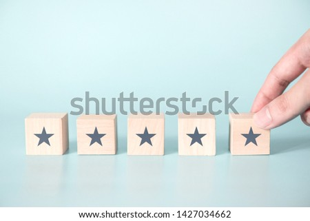 Woman Hand putting wooden five star shape on blue background. Best Excellent Services Rating for Satisfaction. #1427034662
