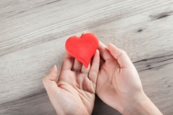 woman hand red heart on the desk background