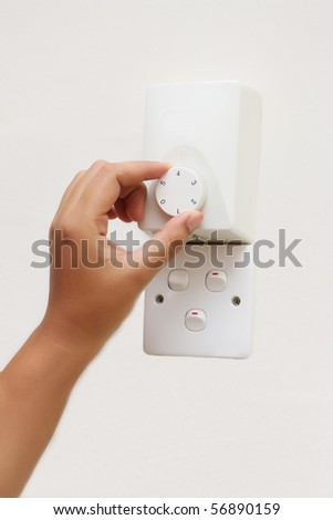 woman hand rotating fan regulator on wall