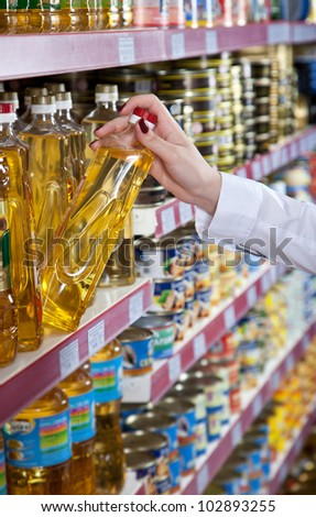 Woman hand selects the bottle of oil at the store