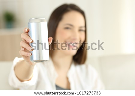 Woman hand showing a soda refreshment can sitting on a couch in the living room at home