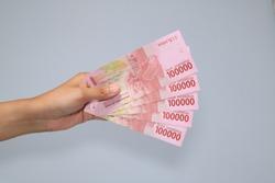 woman hand showing rupiah Indonesian money