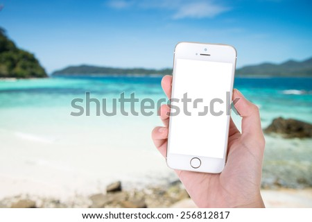 Woman hand showing smart phone with isolated screens display on the beach background