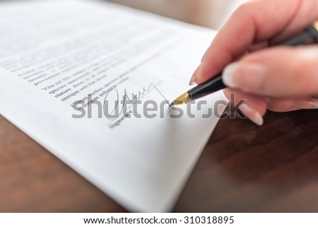Photo of  Woman hand signing a contract