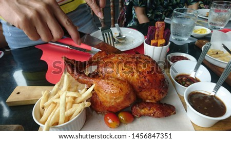 woman hand slashing roast chicken.roast chicken with pepper sauce.  #1456847351