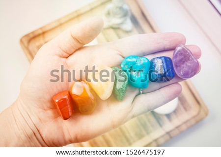Woman hand sowing all seven color chakra crystal stones. Chakra energy flow healer concept.