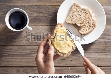Woman hand spreading butter on sliced bread