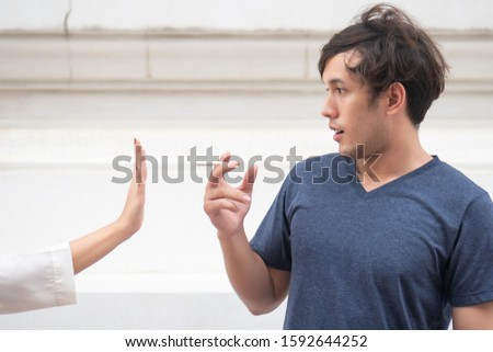 woman hand stopping a man not to smoke; concept of halt, stop smoking, no smoking, smoking prohibited