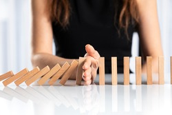 Woman hand stopping falling wooden dominoes effect on white solid ground