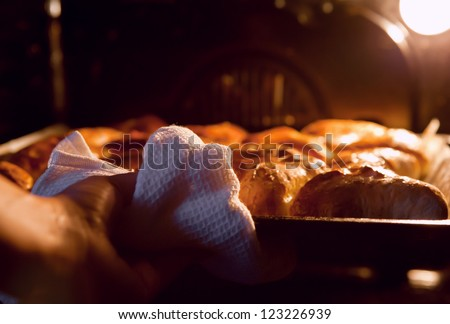 Woman hand taken out hot apple pies from the oven