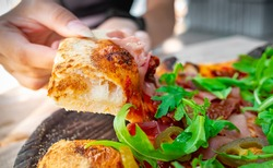 woman Hand takes a slice of meat neapolitan Pizza with Mozzarella cheese, ham, bacon, tomato, Spices and jalapeno in cafe outdoor