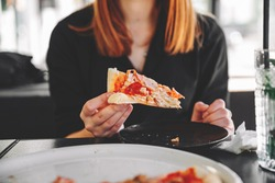 woman Hand takes a slice of meat Pizza with Mozzarella cheese, salami, Tomatoes, pepper, ham, Spices and chicken in cafe