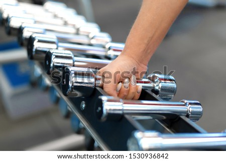 woman hand takes dumbbell form rows of dumbbells in the gym.