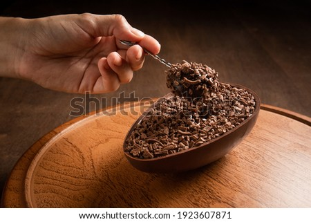 Woman hand taking a spoonful of a stuffed chocolate easter egg on a wooden stand on a wooden table stock photo