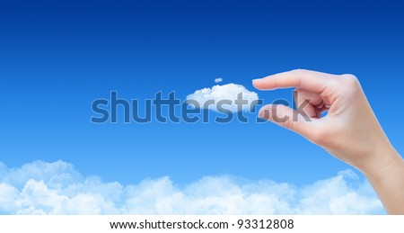 Woman hand taking cloud against blue sky with clouds. Concept image on cloud computing and eco theme with copy space.