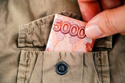 Woman hand taking five thousand ruble bill out of the pocket of a beige jacket. Close-up