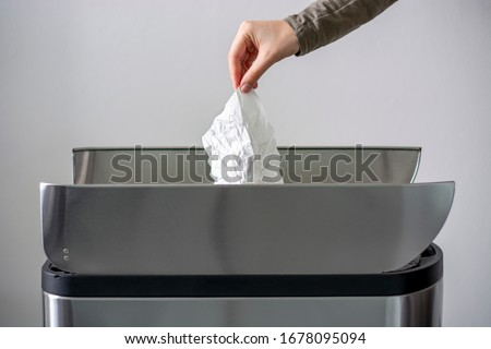 Woman hand throwing a white used crumpled tissue paper handkerchief into a garbage trash bin. Health care and hygiene concept. Coronavirus advice includes use a disposable paper tissue.