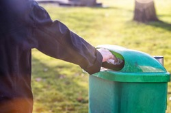 woman hand throwing out garbage in Trash can