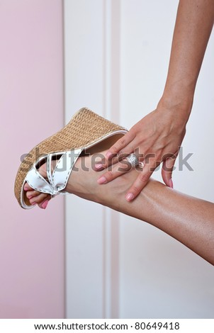 woman hand touching her foot in sandals