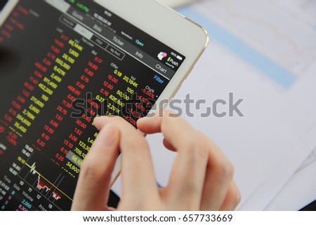 Woman hand Trading online on tablet with business paper and coffee #657733669