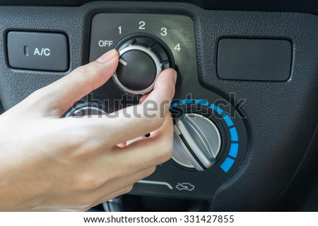 Woman hand turning on car air conditioning system