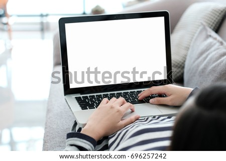 Woman hand typing labtop computer with blank screen for mock up, technology and lifestyle concept