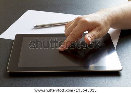 Woman hand typing on touch screen of digital tablet