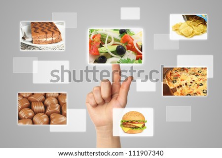 Woman hand uses touch screen interface with food on grey backround