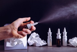 Woman hand using holding nose nasal spray treatment spray bottle and spraying. Fighting the flu and common cold concept. Lot of empty bottles and used dirty paper tissues on background, dramatic light