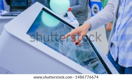 Woman hand using interactive touchscreen display kiosk at futuristic scifi exhibition - close up shot. Education, technology and future concept #1486776674
