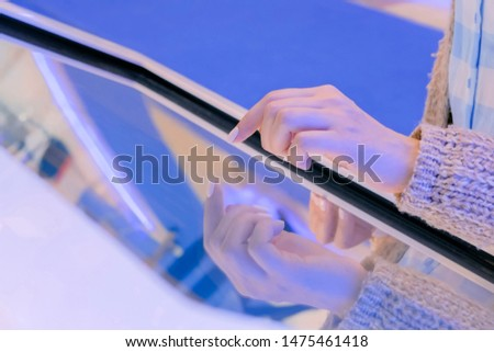 Woman hand using interactive touchscreen display of white electronic multimedia terminal at modern technology exhibition or museum. Education, futuristic and technological concept #1475461418