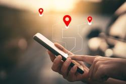 Woman hand using smartphone with gps navigator map icon on blur street background. Technology lifestyle and business travel concept. Vintage filter effect color style.