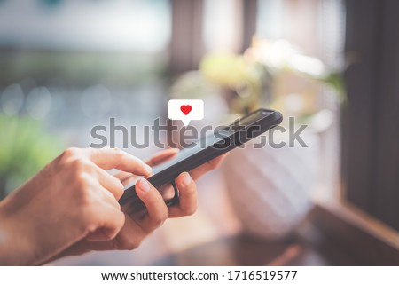 Woman hand using smartphone with heart icon at coffee shop background. Technology business and social lifestyle concept. Vintage tone filter effect color style. ストックフォト ©