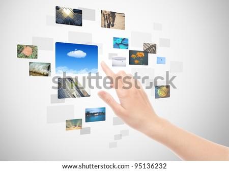 Woman hand using touch screen interface with pictures in frames.