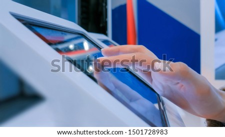Woman hand using touchscreen display of interactive floor standing white tablet kiosk at exhibition or museum - side close up view. Futuristic, education, entertainment, learning, technology concept #1501728983