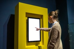 Woman hand using vertical white blank interactive touchscreen display of electronic multimedia kiosk in dark room - scrolling and touching. Mock up, copyspace, template and technology concept