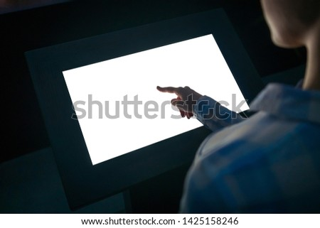 Woman hand using white blank interactive touchscreen display of electronic multimedia kiosk in dark room - scrolling and touching - close up view. Mock up, copyspace, template and technology concept #1425158246