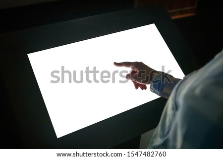 Woman hand using white blank interactive touchscreen display of electronic multimedia kiosk in dark room - scrolling and touching - close up view. Mock up, copyspace, template and technology concept #1547482760