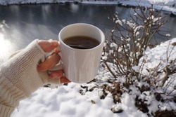 Woman Hand With Ceramic Mug Of Hot Mint Tea. Sun Light And White Snow Background. Winter Time In The Garden.