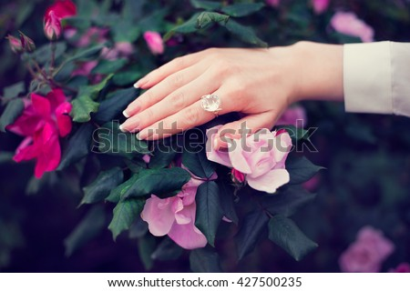 Woman hand with french french manicure and ring on roses flowers #427500235